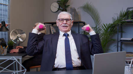 Elderly smiling business man making fitness exercises with dumbbells after hard work while sits at office desk workplace. Senior old confident manager web designer relaxing. Coworking, Freelance