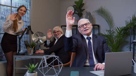 Senior elderly businessman grandfather company director with colleagues team waves palm in hello gesture welcomes someone with hospitable expression expresses positive emotions in office. Coworking Standard-Bild