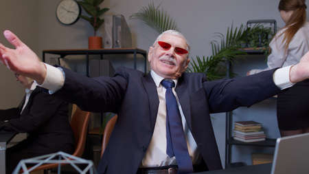 Cheerful mature business company manager working on laptop at desk in office. Senior old businessman raising hands dancing celebrating sudden victory wearing sunglasses waiting for vacation. Coworking