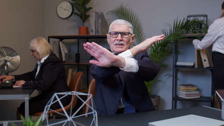 Senior professional businessman grandfather company director showing stop gesture with crossed hands say no in modern office. Displeased elderly mature freelancer man reject refuse proposal. Coworking