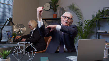 I am strong and independent. Senior confident businessman grandfather company director showing biceps, feeling power strength to fight for job in office. Elderly freelancer man working on laptop