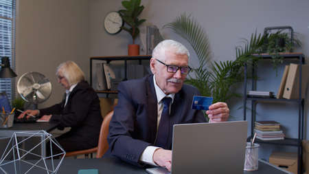 Senior businessman grandfather company director shopping online and paying with credit card in modern office. Elderly mature freelancer man buying on Internet enter credit card details. E-commerce