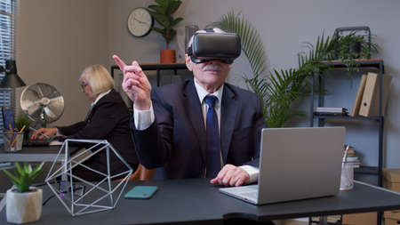 Focused business man entrepreneur using VR app headset helmet doing research. Senior male watching virtual reality 3D 360 video simulation at office. Busy freelancer working on modern tech device