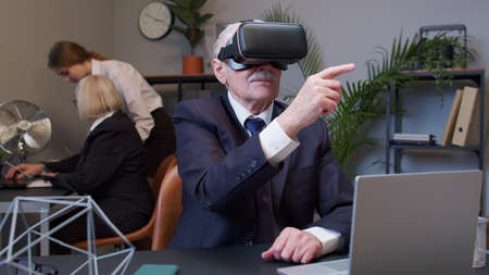 Senior male watching virtual reality 3D 360 video simulation at office. Focused business man entrepreneur using VR app headset helmet doing research. Busy freelancer working on modern tech device