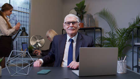 Elderly man boss working in modern office room interior. Senior entrepreneur freelancer concentrated developing new project while looking at camera. Portrait of positive businessman co-worker Standard-Bild