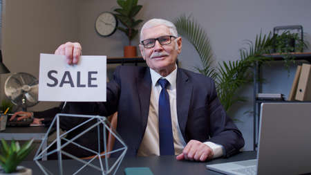 Cheerful senior business company manager showing Black Friday Sale word advertisement inscriptions banner in office. Mature businessman rejoicing good discounts, low prices for online shopping sales