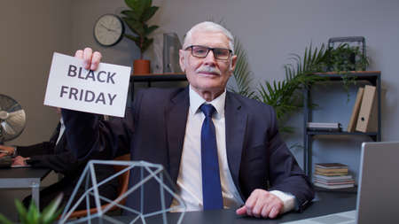 Cheerful senior business company manager showing Black Friday advertisement inscriptions banner in office. Mature businessman entrepreneur rejoicing good discounts low prices for online shopping sales