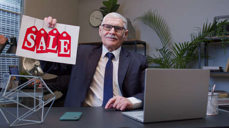 Joyful senior business company manager showing Black Friday Sale word advertisement inscriptions banner in office. Mature businessman rejoicing good discounts, low prices for online shopping sales