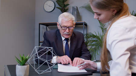 Handsome senior businessman company director explaining documents and discussing project details with young woman colleague while helping her during workday in office. Financial teamwork strategy