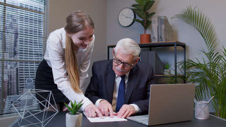 Handsome joyful senior businessman examining financial data and discussing new project with young happy woman colleague in office. Celebrating good financial results of successful teamwork strategy Standard-Bild