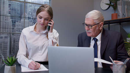 Smiling secretary talking on mobile phone with client. Handsome senior businessman company director boss working on laptop computer sitting in office. Girl in glasses having conversation. Cooperation Standard-Bild