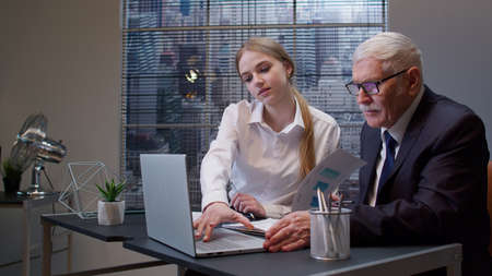 Woman secretary talking on mobile cell phone with client. Busy senior business man boss entrepreneur working, analysis financial graph data in office. Girl having conversation on telephone. Team work Standard-Bild