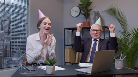 Two joyful happy collegues in formal suits dancing victory dance cheerfully. Rejoicing about developing of new business project. Celebrating success. Diverse motivated business people in modern office Standard-Bild