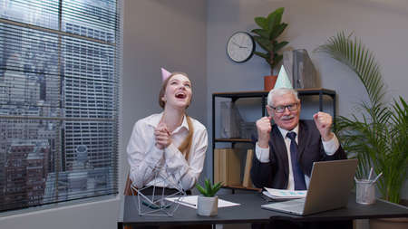Two joyful happy collegues in formal suits dancing victory dance cheerfully. Rejoicing about developing of financial projects. Celebrating birthday. Diverse motivated business people in modern office