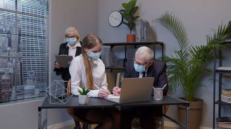 Elderly man boss with woman secretary in medical mask working in office during pandemic. Senior entrepreneur developing new project, sign a contract. Portrait of business people teamwork
