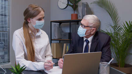 Senior entrepreneur developing new project, sign a contract. Elderly man boss with woman secretary in medical mask working in office during pandemic. Portrait of business people teamwork
