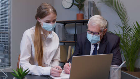 Senior man boss with woman secretary in medical mask working in office during pandemic. Elderly entrepreneur developing new project, sign a contract. Portrait of business people teamwork Standard-Bild
