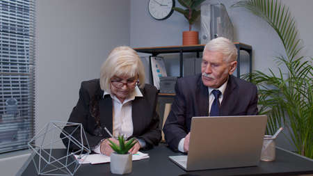 Elderly man boss with woman colleague working in office. Senior entrepreneur developing new project on laptop computer, lady examining financial data documentation from secretary. Business team work Standard-Bild