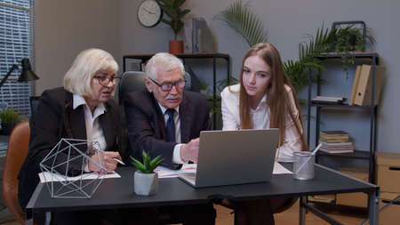 Team of mixed-aged diverse businessman and businesswoman colleague teamwork meeting in office conference room to discussion, explaining, brainstorm business strategy idea for success architect project Standard-Bild