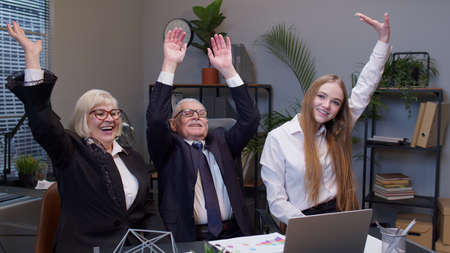 Diverse motivated business people rejoicing developing of business project. Company collegues raising hands in air celebrating corporate unity success good results reward at office