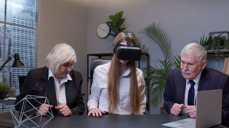 Businesswoman entrepreneur using VR app headset helmet doing research. Senior colleagues watching virtual reality 3D 360 video graph simulation at office. Busy freelancer working on modern tech device Standard-Bild