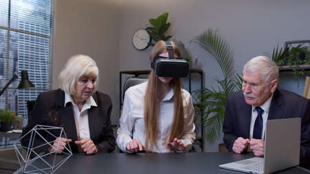 Young woman wearing virtual reality glasses tries 3D app for VR helmet while company colleagues supporting her in modern office. Workers team using innovative future technology through VR headset