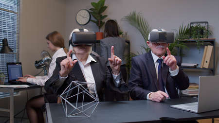Elderly old man boss with woman colleague wearing virtual reality glasses tries 3D app for VR helmet while working in modern office. Workers team using innovative future technology through VR headset