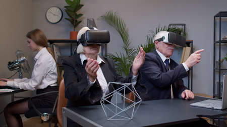 Senior business colleagues using VR app headset helmet doing research. Elderly people watching virtual reality 3D 360 video graph simulation at office. Busy freelancers working on modern tech device Standard-Bild