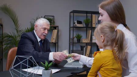 Mother and daughter child kid come to bank office to get a loan for open own business, buy housing. Real estate. Banker man reviews income statement and agrees to provide a loan and giving dollar cash