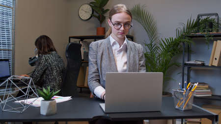 Young businesswoman boss working in modern office interior. Joyful girl entrepreneur freelancer concentrated developing new project while looking on laptop screen. Portrait of positive woman co-worker