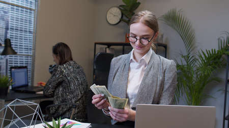 Cheerful rich young business woman manager counting money dollar cash after working on portable laptop at office. Happy female accountant receive finance income. Coworking. Freelance entrepreneur Standard-Bild