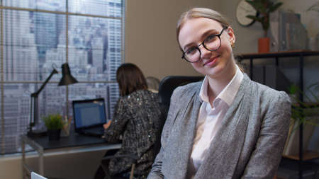 Portrait of concentrated business woman using laptop sits at office desk workplace. Confident female professional manager web designer making online work. Coworking, cooperation. Freelance business