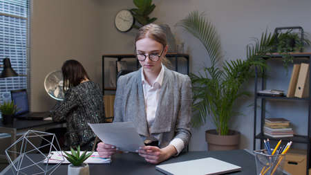Businesswoman accountant reading documents, analyzing financial papers data. Displeased upset young female business company manager irritated sad angry mad after analyzing financial papers in office.