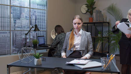 Tired displeased young female business company manager irritated sad angry mad after analyzing financial papers in office. Businesswoman accountant reading documents, analyzing financial papers data