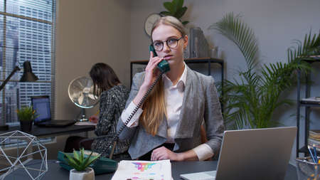 Annoyed young businesswoman executive talking loudly on retro telephone call irritated voice dissatisfied with work arguing at office workspace. Female freelancer boss girl making silly faces, fooling