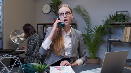 Young annoyed businesswoman executive talking loudly on retro telephone call irritated voice dissatisfied with work arguing at office workspace. Female freelancer boss girl making silly faces, fooling