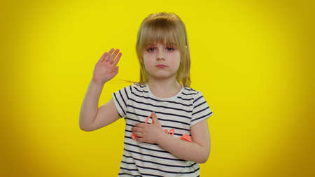 I swear to be honest. Sincere responsible cute kid child 5-6 years old raising hand to take oath, promising to be honest and to tell truth, keeping hand on chest on yellow wall. Children girl emotions