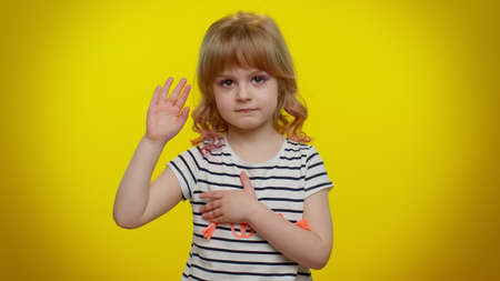 I swear to be honest. Responsible sincere little kid child in shirt raising hand to take oath, promising to be honest and to tell truth, keeping hand on chest on yellow wall. Children girl emotions