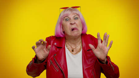 Mature old granny gray-haired grandmother emo making playful silly facial expressions and grimacing, fooling around, showing tongue. Senior woman rocker isolated on yellow background. People lifestyle