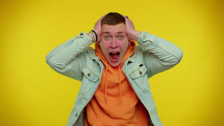 Teenager student boy scared fearful, covering ears with hands, open eyes, meeting his own phobia, evidence horror event, screaming, shouting at loud, freaked out. Young man on yellow background