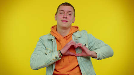 Smiling cute teenager student boy in denim jacket makes heart gesture demonstrates love sign expresses good feelings and sympathy. Young fashionable man isolated on yellow studio background 版權商用圖片