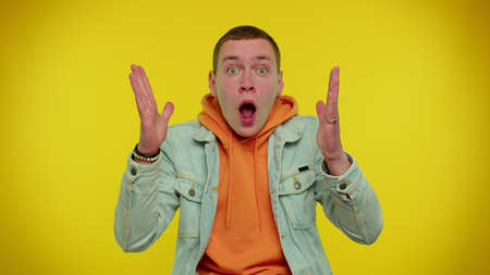 Here you are, found you. Wow. Cheerful teen boy raising hands in surprise looking at camera with big eyes, shocked by sudden victory, meeting someone. Young man isolated on yellow studio background