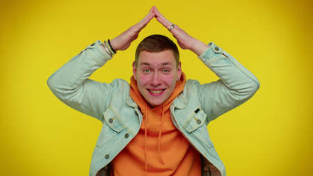 Handsome stylish teen boy playing childish catching up game, feeling in safe making roof above head with hands, insurance, security service. Young man. Indoor studio shot on yellow wall background