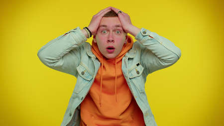 Wow, Oh my God. Excited amazed teen student man 20s raising hands in surprise looking at camera with big eyes, shocked by sudden victory. Sincere young adult guy boy isolated on yellow wall background 版權商用圖片
