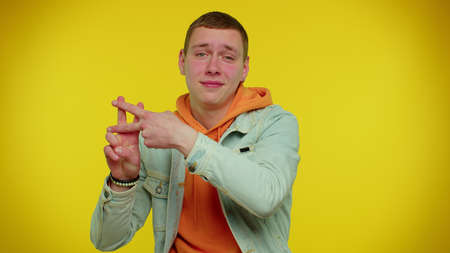 Hashtag. Cheerful teen boy showing hashtag symbol with hands, likes tagged message, popular viral content, sign to follow internet online trends. Young adult man on yellow indoor studio background 版權商用圖片