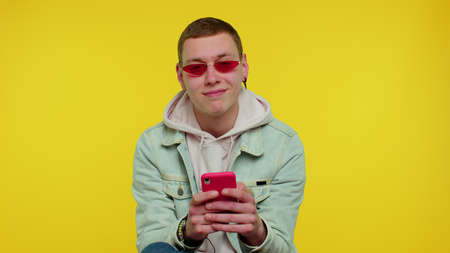 Handsome teenager student boy using mobile phone typing new post on web, sms message, browsing, addiction of social networks. Young fashionable cute man studio shot isolated on yellow wall background