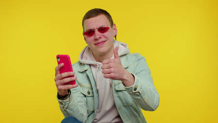 Teenager student boy in denim jacket using mobile phone typing new post on web, sms message, browsing, addiction of social networks. Young fashionable man indoors studio shot on yellow wall background 版權商用圖片