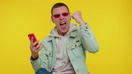 Happy excited joyful stylish teen boy in jacket use mobile cell phone typing browsing say wow yes found out great big win news doing winner gesture. Young adult man on yellow studio wall background
