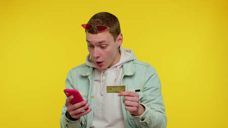 Stylish teen boy use mobile cell phone and plastic credit bank card, browsing say wow yes, found out great big win, doing winner gesture purchases online shopping. Young adult man on yellow background