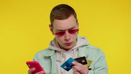 Sincere teen student boy 18 years old in denim jacket using credit bank cards and smartphone while transferring money, purchases online shopping. Young adult man isolated on yellow wall background